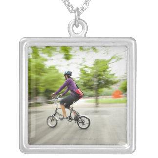 En kvinna som använder en hopfällbar cykel för att silverpläterat halsband