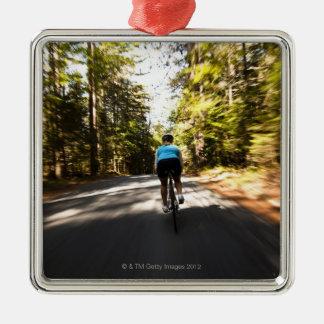 En kvinnlig cyklist rider snabbt på ett litet julgransprydnad metall