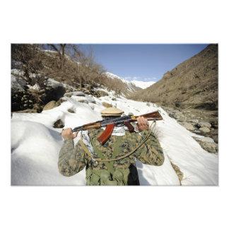 En Mujahadeen vakt går med US-militärmembe Fototryck