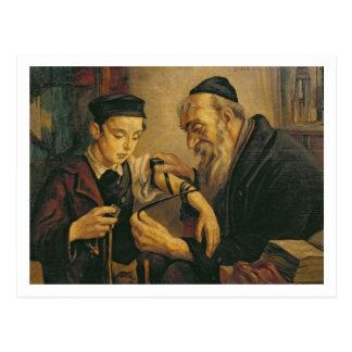 En rabbin som binder phylacteriesna till armen av vykort