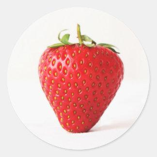 En röd jordgubbeklistermärke runt klistermärke