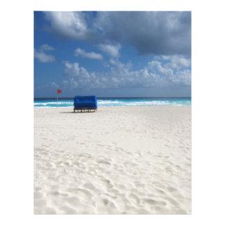 En strandstol väntar på brevhuvud