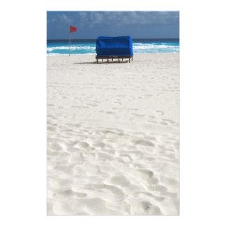 En strandstol väntar på brevpapper