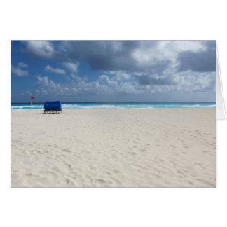 En strandstol väntar på hälsningskort