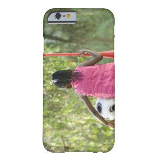 En ung flicka sitter på en ta av planet, innehav barely there iPhone 6 fodral