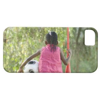 En ung flicka sitter på en ta av planet, innehav iPhone 5 skal
