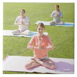 En ung kvinna som gör yoga kakelplatta