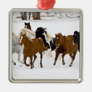 En vinter som är scenisk av rinnande hästar på julgransprydnad metall