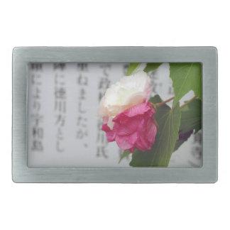 En vit, en rosa blomma och japanska tecken