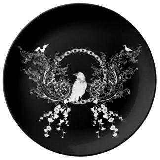 Enorm kråka och blommor i svartvitt tallrikar av porslin