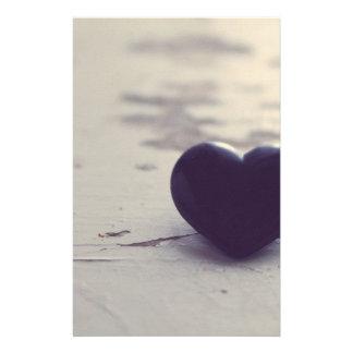 Ensam lilastenhjärta på en våt sandig strand brevpapper