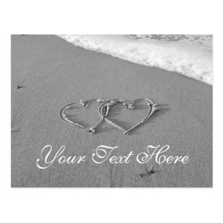 Entwined hjärtor i romantisk strandplats för sand vykort