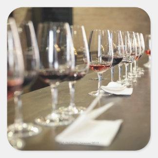 Ett långt ror av vinexponeringsglas ställer in så fyrkantigt klistermärke