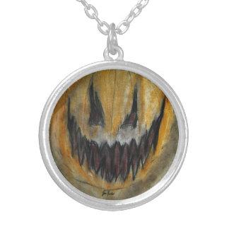 Ett snidit leende på ett pumpaansikte silverpläterat halsband