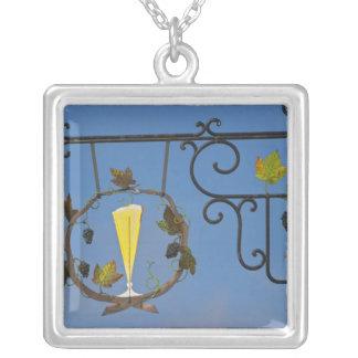 Ett wrought järn undertecknar som illustrerar silverpläterat halsband