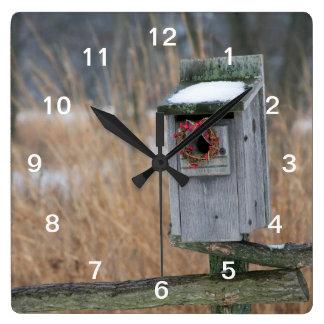 Fågeln bygga bo boxas med helgdagkranen i vinter fyrkantig klocka