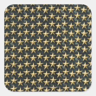 Fält av guld- stjärnor på minnesmärken för fyrkantiga klistermärken