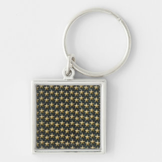 Fält av guld- stjärnor på minnesmärken för världsk fyrkantig silverfärgad nyckelring