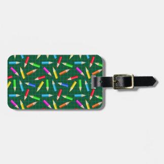 Färgpennor på grönt raster bagagebricka