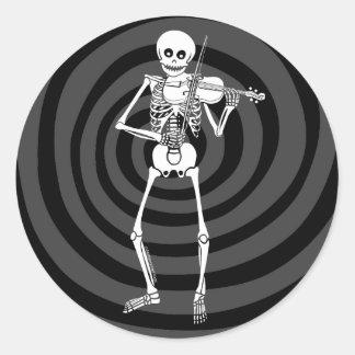 Fiol som leker skelett runt klistermärke