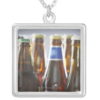 Flaskor av olik buteljerad öl i studio silverpläterat halsband