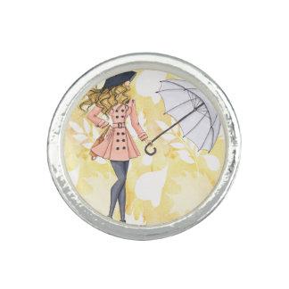 Flicka med paraplyet mot gul höst löv ring