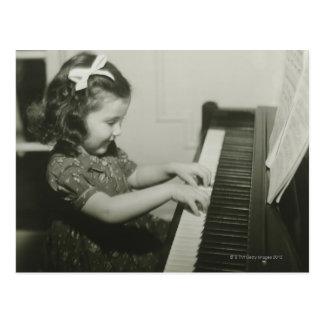 Flicka som leker pianot vykort