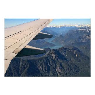 Flygplan som flyger över rocky mountains konstfoto