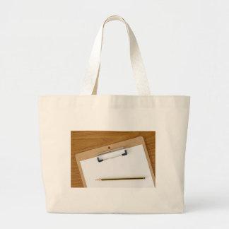 Förbigå papper på en clipboard tote bag
