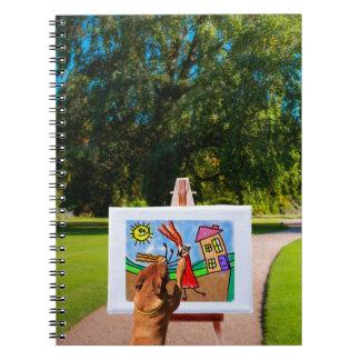 Förfölja att måla en tecknad med borstar i anteckningsbok med spiral