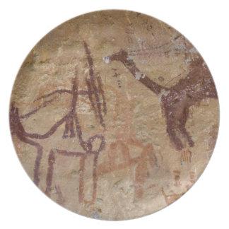 Förhistoriska stenmålningar med kamel och tallrik
