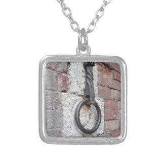 Forntida järnring som hänger på stenväggen silverpläterat halsband