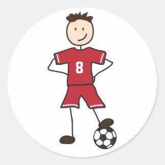 Fotbollspelarefotboll placerar klistermärkear runt klistermärke
