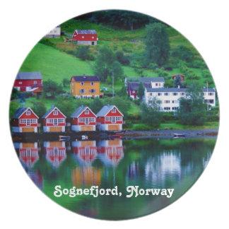 Fotoet av röda hus reflekterade i en norgefjord. tallrik
