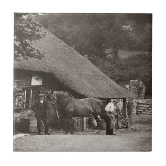 Fotoet för byhovslagarevintage belägger med tegel liten kakelplatta