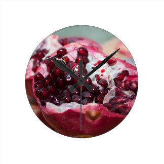 Fotoet för Pomegranatefruktmakroen kärnar ur rött Medium Rund Klocka