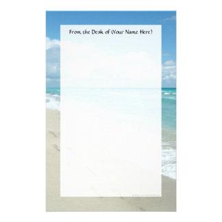 Fotspår på den sandiga stranden för vit, scenisk brevpapper