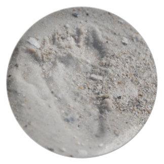 Fotspåret i sanden pläterar tallrik