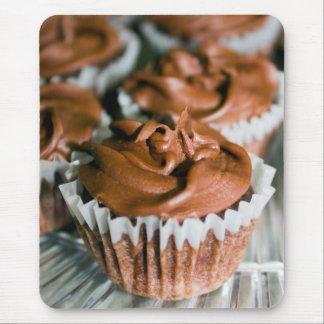 Frostad muffins för choklad på ett pläterafoto musmatta