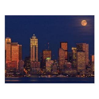 Fullmåne som stigning över i stadens centrum vykort