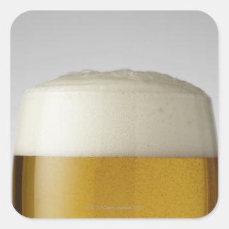 Fullt exponeringsglas av öl inomhus fyrkantigt klistermärke