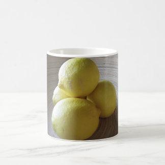 Fyra citroner i bunke kaffemugg