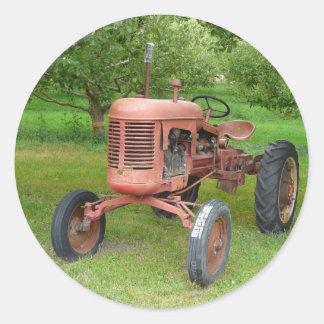 Gammal traktor i fruktträdgården runt klistermärke