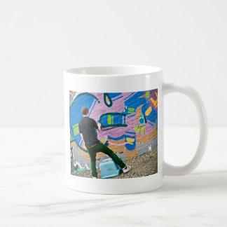 Gatakonstnär som gör saker kaffe muggar