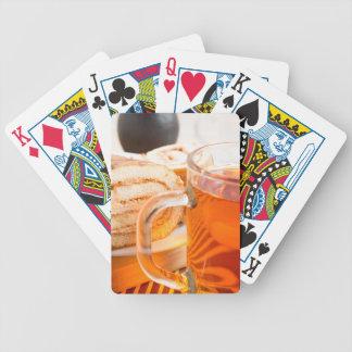 Genomskinlig glass mugg med varm tea och choklad spel kort