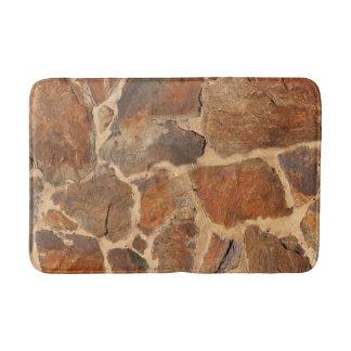 Geologistenväggen strukturerar den guld- orangen badrumsmatta