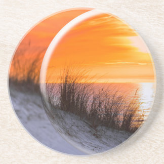Glass sphere som reflekterar orange solnedgång underlägg sandsten