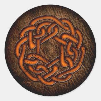 Glödande orange celtic prydnad på läder runt klistermärke