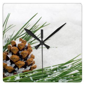 Grankotten och gren med snö kvadrerar väggen tar fyrkantig klocka
