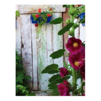 Grekisk blåttdörr i blomsterträdgård i Grekland Vykort